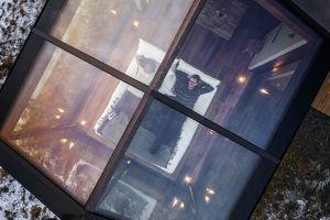 A birdseye view of a couple relaxing in the Panorama Glass Lodge during daylight