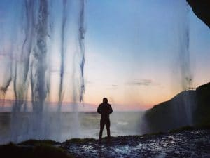 Standing under a waterfall in Iceland at sunset