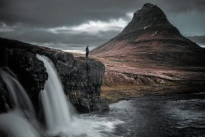 A man standing looking at Kirkjufell with Kirkjufellfoss waterfall in the foreground