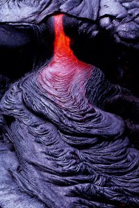 Pouring lava cooling on dark rocks