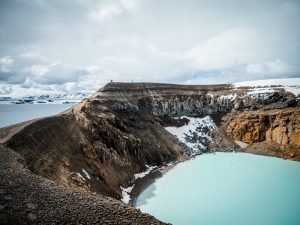 A blue crater lake in the Icelandic Highlands under a cloudy sky