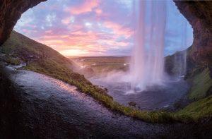 the midnight sun in Iceland from behind Seljalandsfoss waterfall
