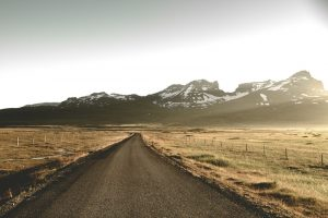 a gravel road in Iceland under the midnight sun with mountains in the distance