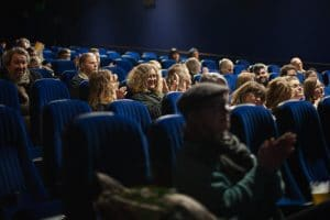 Bio Paradis audience in blue seats watching a film