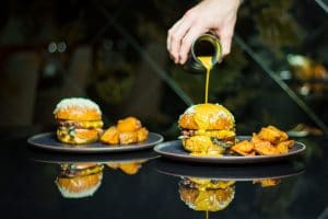 Kól Restaurant food advert showing a burger with bernaise sauce being poured onto it