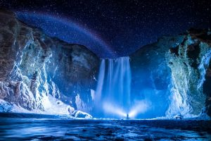 Skogafoss waterfall on Iceland's south coast at night with a person shining a torch on it