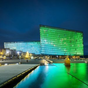 Harpa Concert Hall in Reykjavik with green lights projected on the outside in the evening