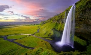 a long exposure of Seljalandsfoss waterfall in Iceland under the midnight sun