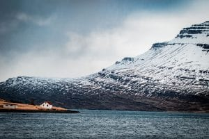 a house sitting at the base of a fjord in Iceland's eastfjords with a snowy mountain in the background