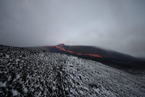 Geldingadalir erupting volcano in the distance on a foggy day in Iceland with low cloud