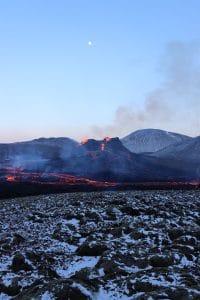 Geldingadalir erupting volcano shooting lava under a blue sky