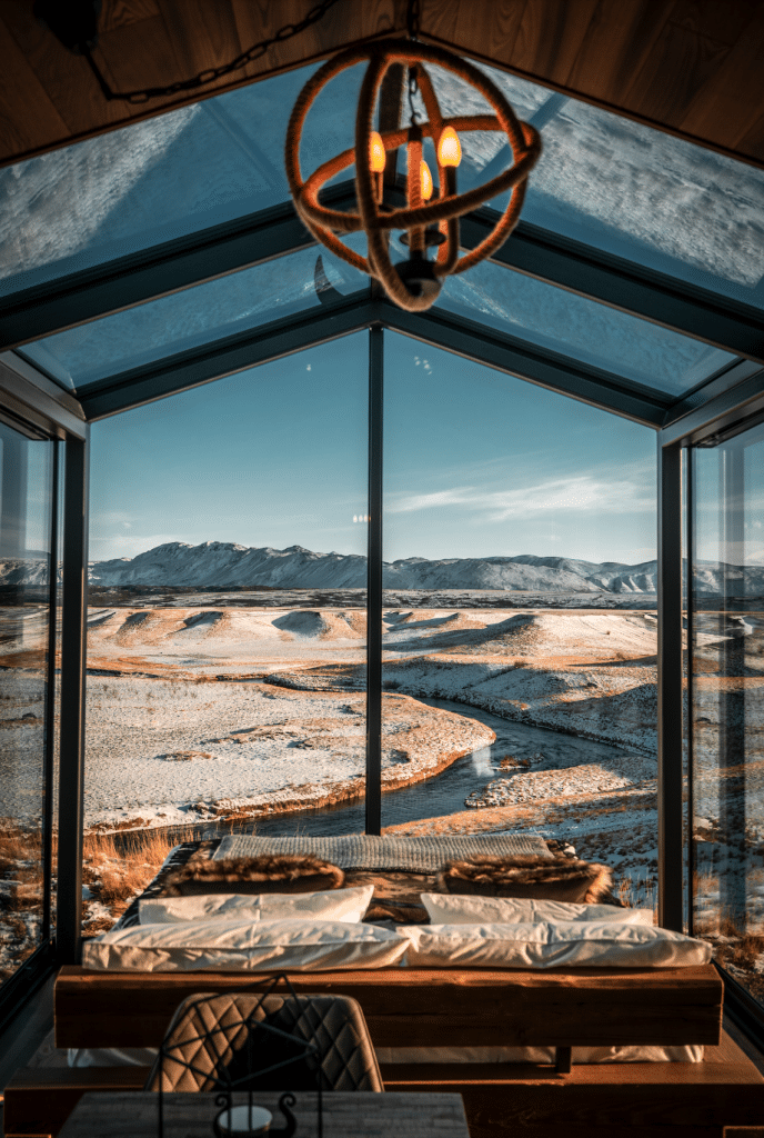 A bright blue sky and snowy mountains from inside the Panorama Glass Lodge