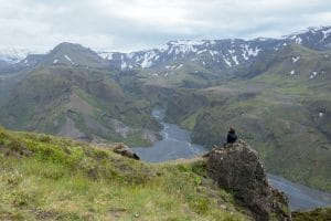 A person sitting on top of the Mountain ridge of Thorsmork in the Icelandic Highlands