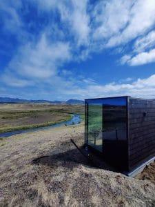 The Panorama Glass Lodge sauna under a blue sky